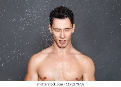 Hydrated muscle stripped male model portrait in water splash and drops on grey isolated font background