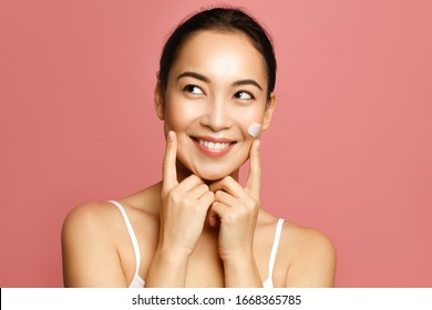 Hydrating and moisturizing. Young Asian woman applying face cream smiling and touching her cheeks against pink background