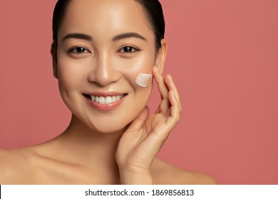 Hydration and skin care concept. Young beautiful asian model posing with applayed cream on her face