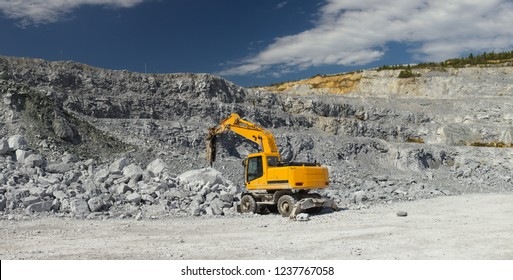 Hydraulic breaker breaks rocks in a quarry, panorama. Mining industry.