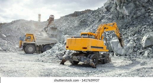 Hydraulic breaker, close-up, working in a stone quarry, with heavy mining dump truck during of loading in the background, panorama.