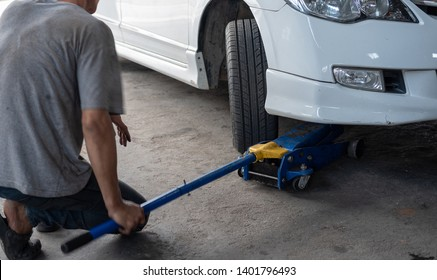 Hydraulic car jack to lift car for check the wheel.