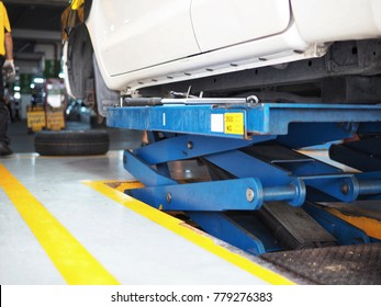 A hydraulic car lifter are working in the garage.