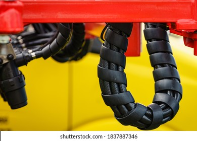 Hydraulic connections hoses in black spiral guard wraps. Machinery industrial detail