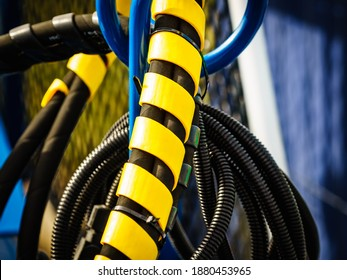 Hydraulic connections hoses in black and yellow spiral guard wraps. Machinery industrial detail