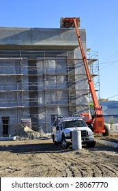 A hydraulic crane is used to lift construction material to roof of new building