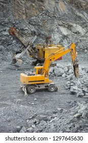 Hydraulic hammer and mining truck in the quarry of a mining enterprise.