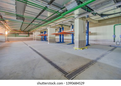 Hydraulic lift or mechanical jack for repair and storage of car in underground parking. Modern underground parking without cars. Signs and boards indicating directions.