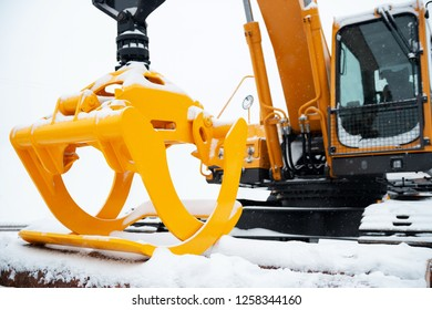 Hydraulic manipulator. Yellow log loader. Forestry equipment for moving wood and other materials. Heavy diesel tractor, industrial machinery. Winter time