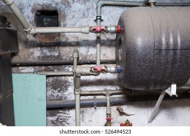 Hydraulic pipes an valves in basement. Home heating system in close up.