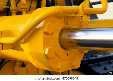 Hydraulic piston against the sky. a fragment of a yellow bulldozer