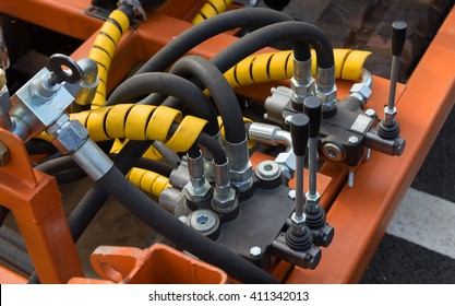 Hydraulic tubes, fittings and levers on control panel of lifting mechanism