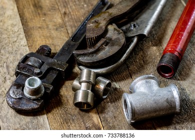 Hydraulics, tools for plumber on wooden table. Workshop, table and tools - adjustable spanner, connectors, keys. Black background