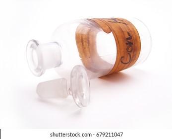 Hydrochloric Acid Bottle - An empty glass hydrochloric acid bottle and stopper rest on their sides on a white background.
