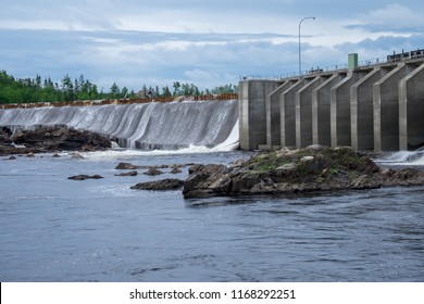 An hydroelectric dam with water spilling over the dam.  The sky is blue and there's white clouds. The water is causing foam to collect at the bottom of the wall. There are large boulders in the river.