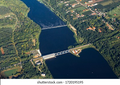 Hydroelectric plant on a small river. Aerial photo of a dam taken from plane. Landscape of fields, forests and water. Polish village near to river