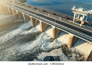 Hydroelectricity power station gates with flowing water, aerial view.