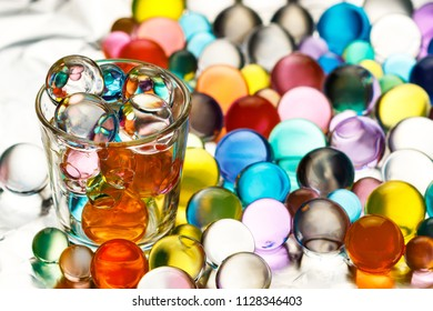 a lot of hydrogel balls on aluminum foil and a vodka pile filled with hydrogel balls of different colors