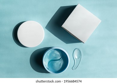 Hydrogel cosmetic eye patches for skin care on blue pastel background. Product for skin lifting, anti-aging wrinkles. under eyes patches in a blue container. Cosmetics mockup.
