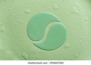 Hydrogel green eye patches on green background with water drops close up. Cosmetic moisturizing under eye patches with collagen.