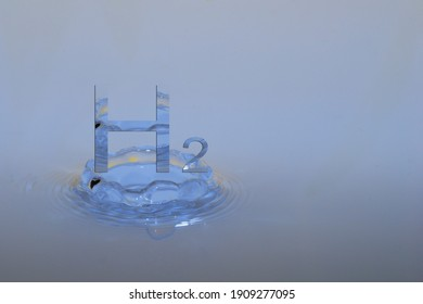 hydrogen h2 letters hovers over a drop impact in a blue fluid