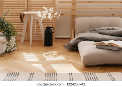 Hygge bedroom with scandinavian futon as a bed next to white flowers in black vase and wooden coffee table, real photo