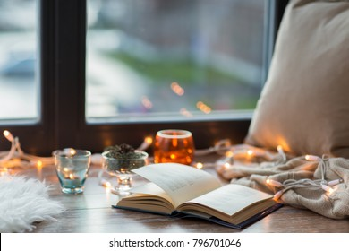 hygge and cozy home concept - book, garland lights and candles on window sill