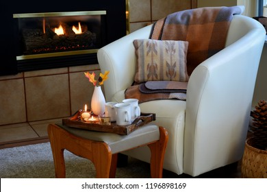 Hygge home comfort with soft leather bucket chair, candles, blanket and tea beside gas fireplace.  Horizontal format in natural light