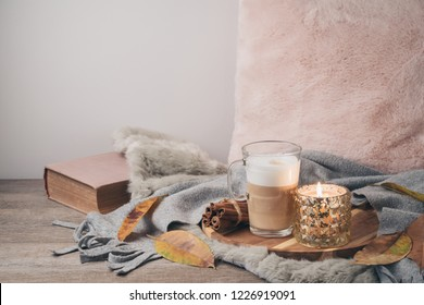 Hygge Scandinavian style concept with latte macchiato coffee cup, candles and book. Cozy winter or autumn composition