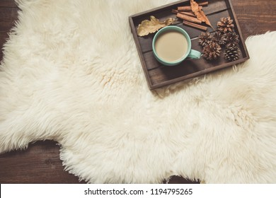 Hygge still life with hot cup of masala tea, anise, warm scarf on wooden board. Copy space. View from above.