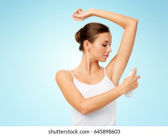 hygiene, bodycare and people concept - beautiful young woman applying antiperspirant or spray deodorant over blue background