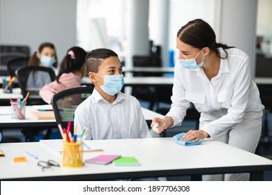 Hygiene And Cleaning. Teacher cleaning table with antibacterial sanitizer and napkin, disinfecting surface, applying antiseptic spray on desk, wearing disposable face mask, boy studying in classroom