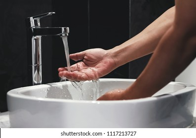 hygiene concept, a man washing hands in the bathroom