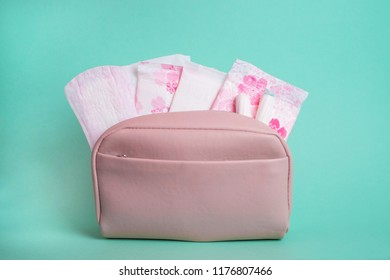 Hygiene feminine pads and tampons in pink beauty bag on green background.
