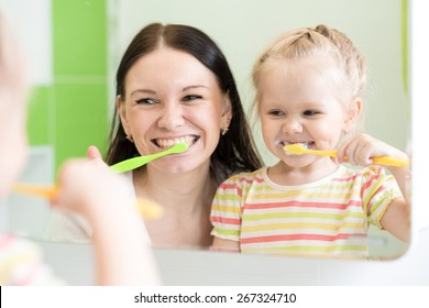 Hygiene. Happy mother and child girl brushing teeth together