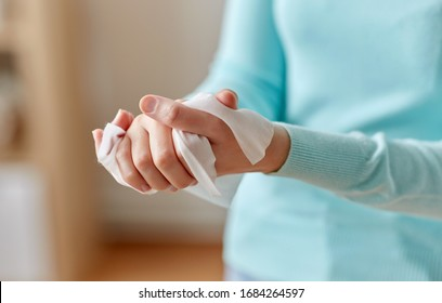 hygiene, health care and disinfection concept - close up of woman cleaning hands with antiseptic wet wipe