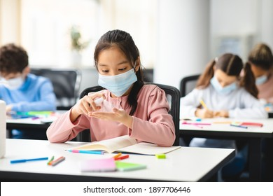 Hygiene And Health Concept. Asian girl applying antibacterial sanitizer spray on hands, wearing protective medical mask, sitting in classroom at school. Prevent the spread of infection and germs