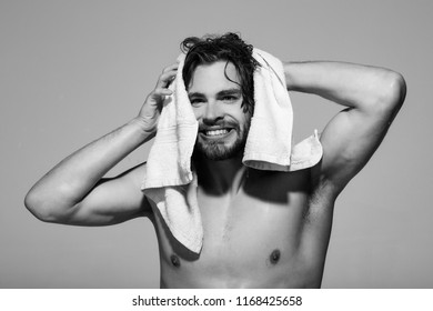 hygiene and morning, naked smiling man with muscular wet body hold towel in bath or shower after washing on grey background, skincare, health and wakeup, everyday life, barbershop