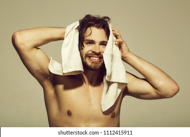 hygiene and skincare. hygiene and morning, naked smiling man with muscular wet body hold towel in bath or shower after washing on grey background, skincare, health and wakeup, everyday life