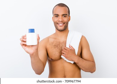 Hygiene, vitality, beauty, men life concept. Young smiling nude afro guy with towel and product in his arm is making advertisement
