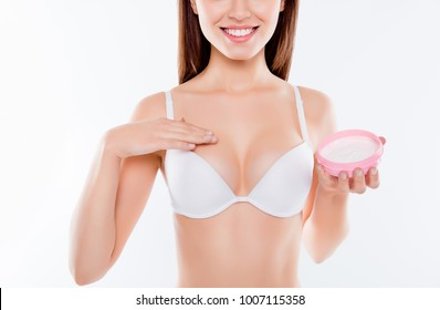 Hygiene wellness rejuvenation clean clear medical natural concept. Cropped close up photo of beautiful pretty woman applying gel for breast augmentation, pink jar on palm isolated on white background