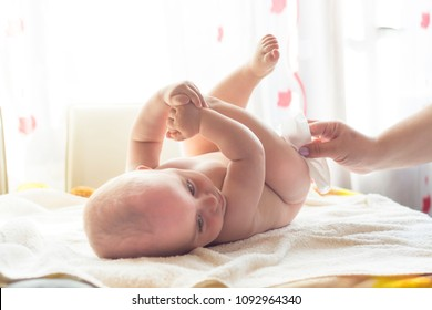 Hygiene - young momy wiping the baby skin with wet wipes. Cleaning wipe, pure, clean