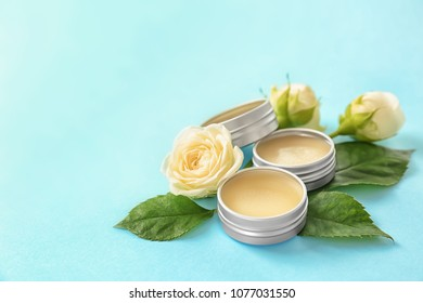Hygienic lip balms and flowers on color background