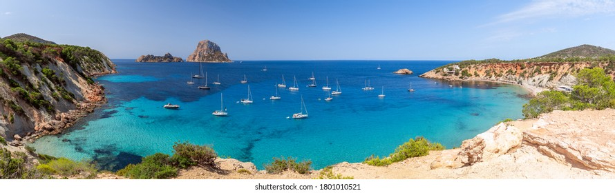 Hyper panorama of Cala Hort with sea sailing yachts and the mountain Es Vedra. Ibiza, Balearic Islands, Spain