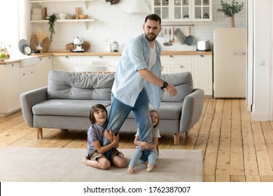 Hyperactive kids holding tired upset father legs when they want to relax. Frustrating dad stressful feels heaviness and headache at home. Fatigue man does n't not want to play with son and daughter.