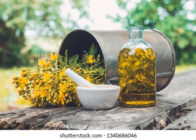 Hypericum - St Johns wort flowers, oil or infusion bottle, mortar and big vintage metal mug of Hypericum flowers on wooden board outdoors.