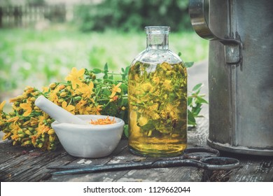 Hypericum - St Johns wort plants, oil or infusion transparent bottle, mortar on wooden table outdoors.