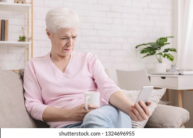 Hyperopia. Woman squinting and holding phone far from eyes, reading smartphone screen