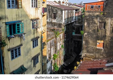 Hyperrealistic city scape: the old town houses with flaky paints and sprouted greens and narrow street in Yangon (Rangoon, Rangun) - the capital of Myanmar (Burma), South East Asia
