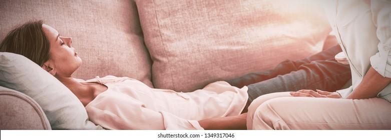 Hypnotherapeut, der Pendelblume hält, durch Patient auf dem Sofa zu Hause